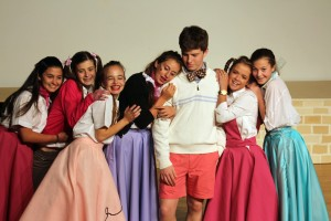 """Sarah F. (center), playing Kim McAfee, is joined by her girlfriends as they swoon over Hugo, played by Connor H., in the musical number """"One Boy"""" during the production of Bye Bye Birdie."""